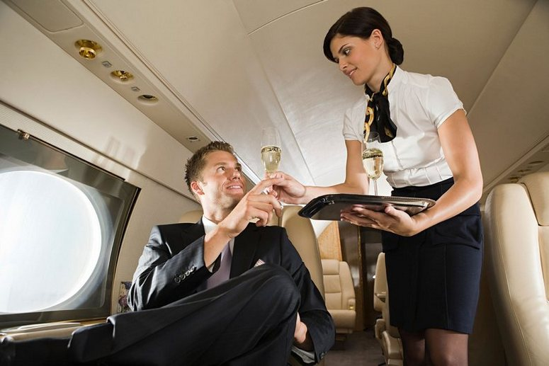 A happy passenger on a private jet receives champagne from an air hostess.  It looks like the air vents in the cabin ceiling are plated with gold.  Gold.