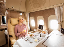 Lady sits in comfort in her own private dining area eating chef prepared food on a regal wings luxury jet
