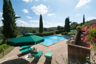 The pool, patio area, and gardens with distant pine forests and bright blue sky at Poggio Villa