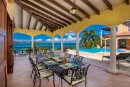 Outdoor dining area under shade looking at the pool at Villa Ariana
